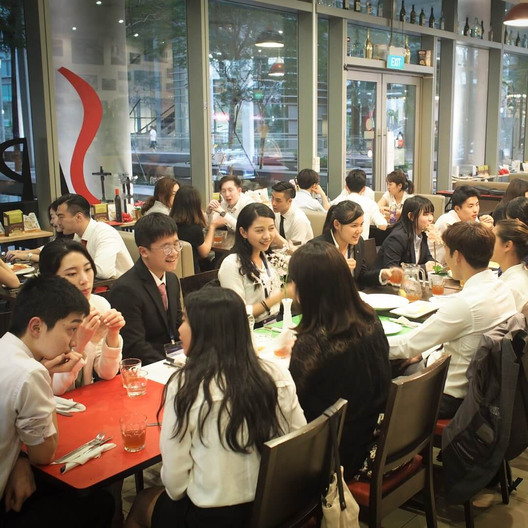 Group of students eating and talking at restaurant